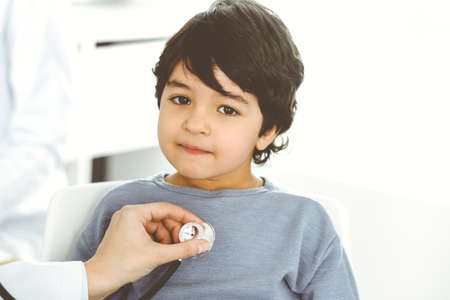 Doctor-woman examining a child patient by stethoscope. Cute arab boy at physician appointment. Medicine concept