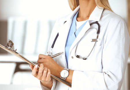 Unknown woman-doctor at work in clinic. Female physician controls medication history record and medical exam results, close-up. Medicine concept