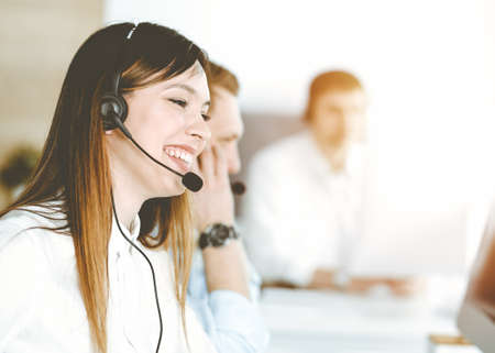 Asian woman working at customer service office. Business concept. Group of diverse operators at work in sunny call center.
