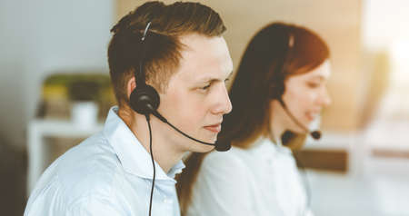 Businessman working at customer service office. Group of diverse operators at work in sunny call center