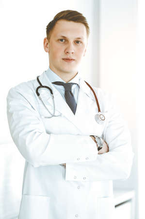 Man-doctor standing straight in sunny clinic. Medicine concept Foto de archivo