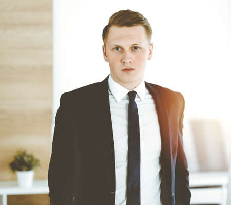 Cheerful businessman standing and looking at camera in sunny office. Headshot of young entrepreneur
