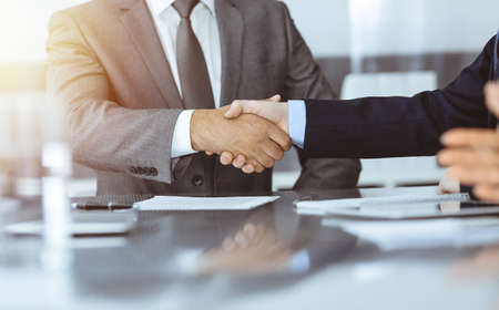 Unknown business people are shaking hands after contract signing in modern office, close-up. Handshake as successful negotiation ending