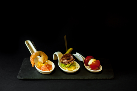 snacks in spoons. Shrimp, Salami and Caprese Stock Photo