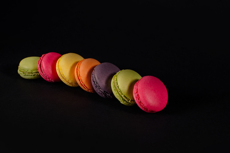 colored macaroons on a black background. red, yellow, pink, green, brown macaroon. Knit sweater, palm on a black background. A palette of bright colors, a stove, a dietary cookie. Elite baking Stockfoto