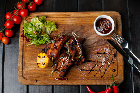 Grilled ribs with valerian, rosemary, corn and salad on a wooden board Stock Photo