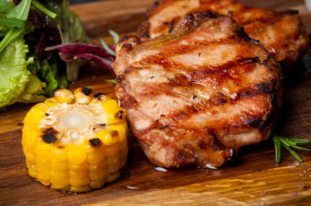 two grilled steaks with corn and salad on a wooden plank