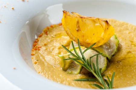 Pumpkin cream soup with fish som. A dish at a restaurant for Halloween celebrations. Black background, brick wall and wooden table Stock Photo