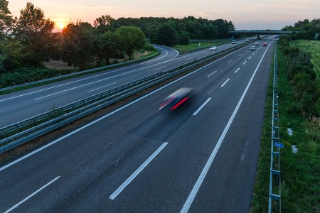 autobahn: german highway at sunset with light trails from passing cars