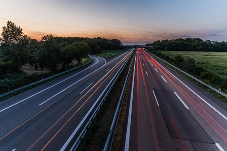 highway: german highway at sunset with light trails from passing cars