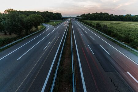 light trails: german highway at sunset with light trails from passing cars