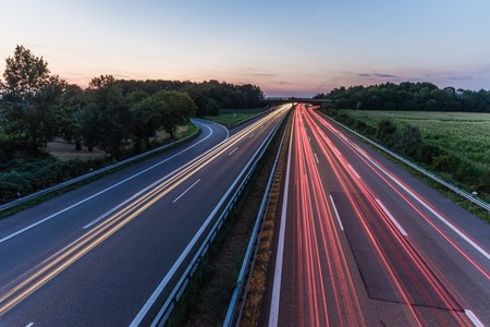 german highway at sunset with light trails from passing cars