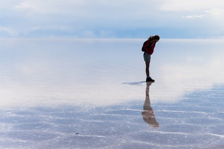 salt flat: girl standing on the wet salt flat of uyuni