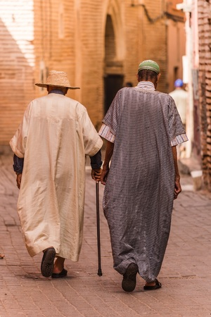 clothed: two traditionally clothed moroccans walking in the medina