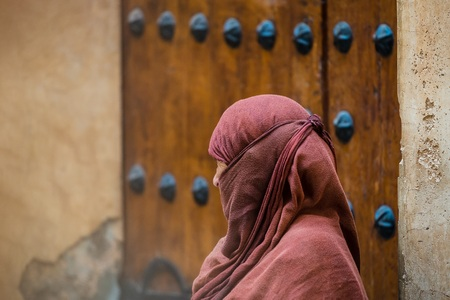 clothed: a traditionally clothed moroccan woman walking in the medina Stock Photo