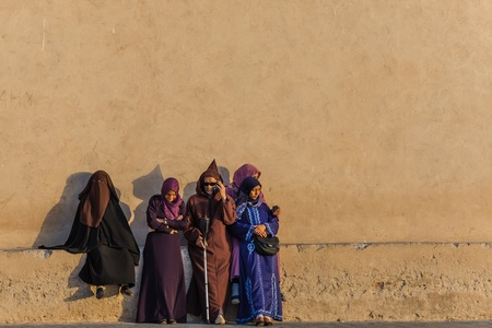 modesty: essaouira, Morocco - Circa September 2015 - arabic traditionally dressed people standing in the sunset