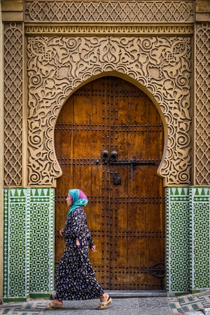 caftan: fes, Morocco - Circa September 2015 - a traditionally dressed lady in front of an old medina building