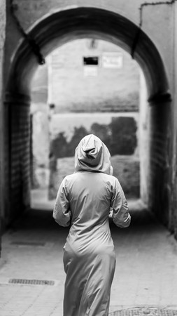 clothed: traditionally clothed arabic woman walking in the medina of marrakech Stock Photo