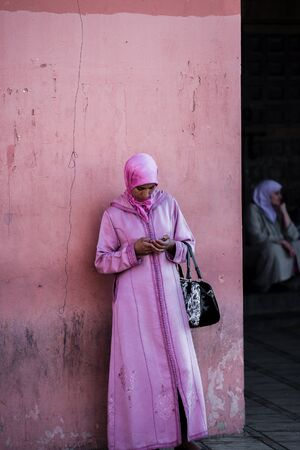 clothed: marrakech, Morocco - Circa September 2015 - a traditionally clothed woman using her smartphone