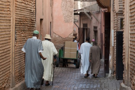 clothed: traditionally clothed moroccans walking in the medina