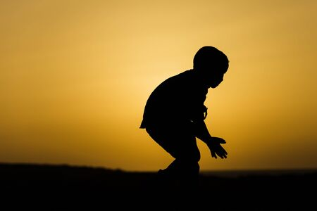 sihouette: sihouette of a boy in front of the setting sun Stock Photo