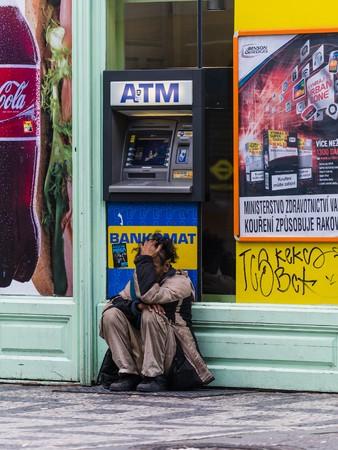 poor man: prague, czech - circa november 2015 - a poor man in front of an atm
