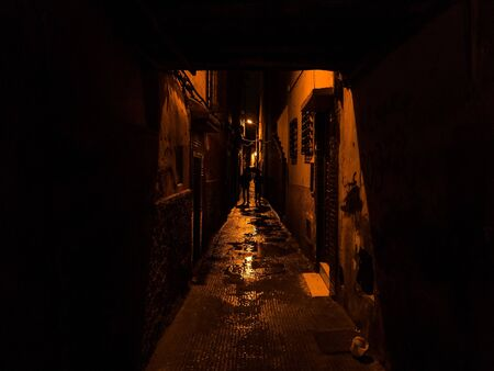suspense: two silhouettes walking in a narrow street in marrakesh - suspense thrilling lowkey exposure Stock Photo