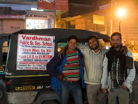 tuk tuk: jaipur, India - Circa December 2015 - three indian people posing in front of a tuk tuk