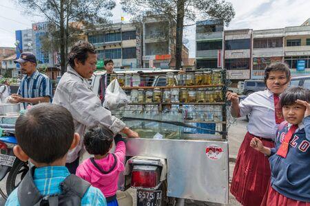 street vendor: Berastagi, Indonesia - Circa June 2014 - A street vendor selling fishes to children