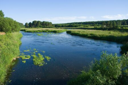 Tranquil river flowing through the meadows before the sunset photo