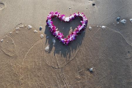 Wave washing over Dendrobium heart shaped lei on Kihei Beach, Maui