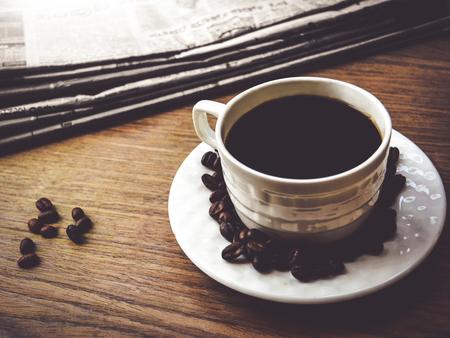 Taza de café con granos de café y periódico Foto de archivo - 92435121