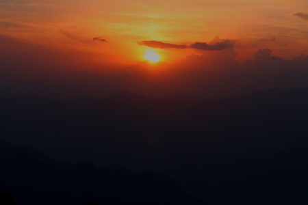 Sunset in the Himalayas of Uttarakhand, India, with a silhouette landscape of the mountains in the front.