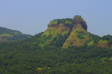 A prominent hillock with dense forests covering the base in the western ghats of Maharashtra, India