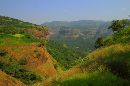 Rocky valleys and Hills of the Western Ghats of Maharashtra, India with the backwaters of Bhira Dam as seen from the trail to Andharban on a clear sunny day.