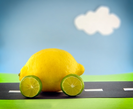 A lemon car with lime wheels driving along a construction paper scene.  Scene made by the photographer.  photo