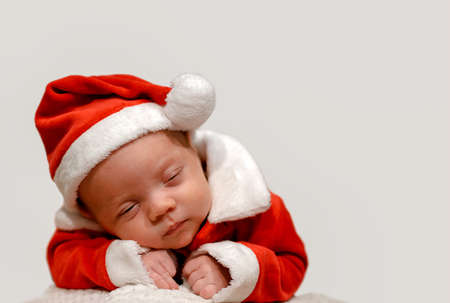 christmas baby: A baby in a Santa suit dreaming