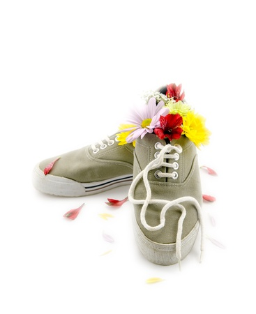 A contradiction concept.  A pair of stinky sneakers with fragrant flowers in them.