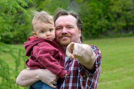 Father holding and pointing with toddler son