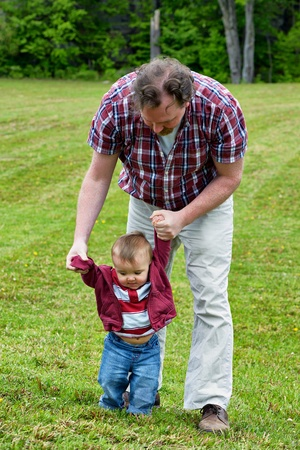 vaderlijk: Vader helpt zoon peuter om te leren hoe te wandelen in een buitenomgeving Stockfoto