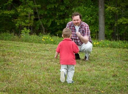 vaderlijk: Father holding a dandelion while his son, a young boy, walks towards him.