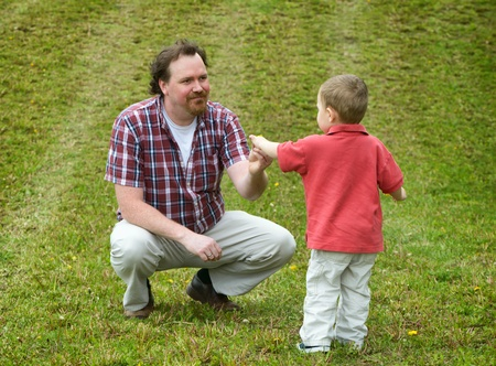 Father and Son interacting outdoors in a grassy field. Banco de Imagens