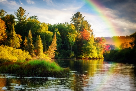 A scenic lake or river during a light rain displaying a rainbow in the mist on an autumn day close to sunrise or sunset