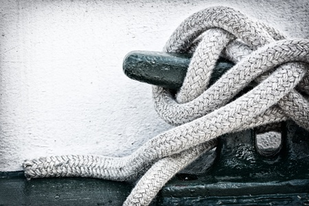 A detailed closeup macro of a rope mooring line fastened to a cleat. Space for copy. photo