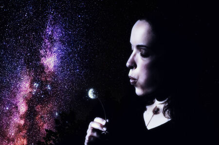 A young woman blows on a dandelion and makes a wish illuminated by the Milky Way of the night sky   photo