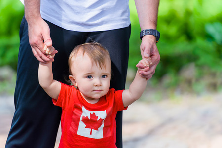 Toddler in Canada Flag shirt walking assisted by his father  Room for copy space