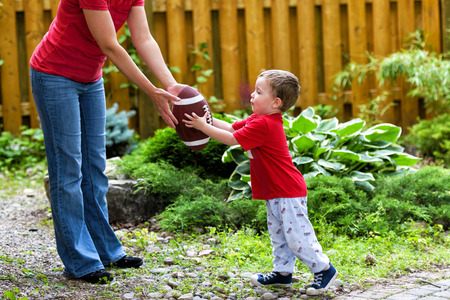 A small boy receives a hand off from his mommy in a game of backyard football