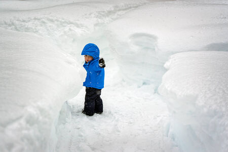 taller: A small toddler boy points the way as he attempts navigate pathways carved in snow accumulation taller than he is  Typical winter weather within the lake effect or snow belt  regions of United States and Canada     Stock Photo