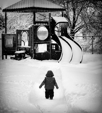 b w: Small child looks longingly at the local playground which is dangerously covered in snow and ice