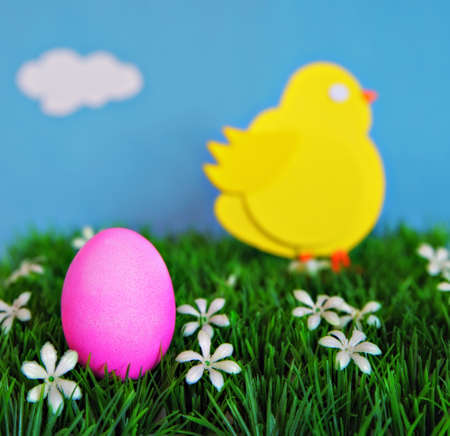 An Easter concept depicting a pink colored Egg in the foreground spring grass